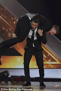 Jahmene Douglas and James Arthur both take turns in lifting each other after learning they are the last two acts left in the X factor UK