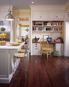 Love how the cupboards go to the high ceiling, the corbels and wood desk top. Dark stained floor ~