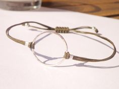 Adjustable sterling silver karma bracelet on khaki/green waxed linen