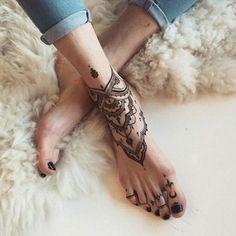 schwarzes Knöchel  und Zehentattoo, Frau mit Jeans und schwarzem Nagellack auf den Zehen