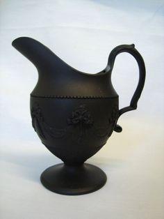 AN ANTIQUE  BLACK BASALT  STONEWARE CREAM JUG. NR  £30