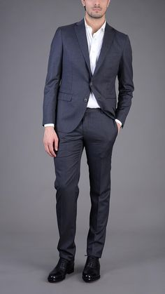 Dark gray pinstripe three button single breasted blazer with matching four pockets classic trousers. 100% merino wool. Size 50.