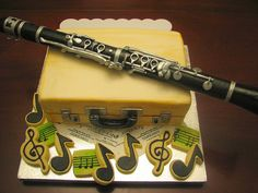 Clarinet cake, EVERYTHING is edible!   Description: Clarinet out of gum paste, it is actually the size of a real clarinet! The case is the cake covered with fondant and painted with food coloring. The music notes are shortbread cookies. The music is printed on icing sheets with edible ink. The whole thing is edible!! By maryknsweetcakes