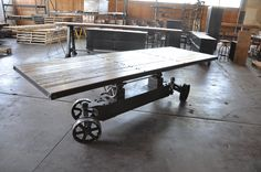 """Four Seasons Train table is done! Top height adjusts from dining to bar height (30"""" - 42""""), and it has an extra worn 2"""" thick oak top. This will sit outside at the Four Seasons restaurant """"Proof"""" on an infloor track. It has locking wheels, four wheel steering, 12.5"""" custom wheels, weighs 550 lbs, and was ALL handmade in America by Vintage Industrial in Phoenix."""