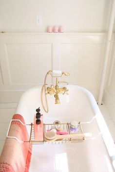 Pamper yourself in style! Take inspiration from this spotless white and gold bathroom theme. A freestanding bathtub oozes glamour and this gold wire bathtub caddy is perfection. #pampering #metime #homespa