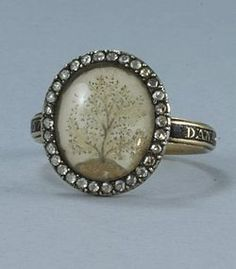 """Georgian mourning ring inscribed """"Dan Gass Ob 28 July 1773 AE 57"""". Macerated hair set on ivory creates this vignette of the symbolic tree of life , barren of colour against a clear sky. The ring is set with rose cut diamonds. Of English origin."""