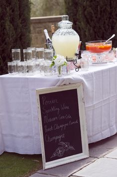 outdoor wedding ideas-table and punch pitcher and chalkboard frame