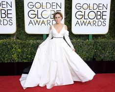 Actress Sarah Jessica Parker wore a bridal-inspired look by Vera Wang Collection on the red carpet of the 74th annual Golden Globes. She wore a beautiful, silk, ivory-color gown featuring a plunging V-neck, sleeves, and a draped skirt.