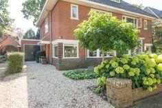 Jaren30woningen.nl | Klassieke voortuin met oprit van grind