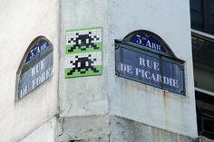l'artiste français nommé invader utilise la mosaïque sur cet image il travaille sur un mur de Paris.