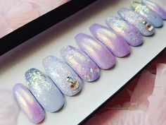 This stunning set has an iridescent chrome unicorn effect, over a base of periwinkle blue and lilac! The index finger nails has angel foil embedded within clear gel, and the accent nails have a beautiful multicolored light peach/pink glitter with genuine Swarovski crystals! The ring