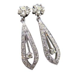 Exquisite Panetta earrings feature rhinestone clusters in silver pave with drop dangle design featuring a swing accent in the center of long tear drops and polished finish.