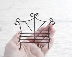 """Fairy Garden Bench - Miniature Rustic Metal Wire Furniture A lovely littlefairy garden bench for your miniature garden. It is made out of sturdy metal wire in a dark brown color. It has a really pretty shape with curly spiral details. It looks beautifulon it's own, or you can place two together with a rock or wood slice """"table"""" between them to make a darling little seating area. Dimensions: Measures 3 1/2 inches long, and 2 1/2 inches tall."""