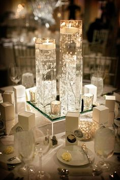 Wedding table setup for winter weddings idea. Use tall vases and sparkling table top decorations such as votive tea light candle holders
