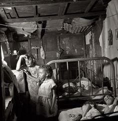 "January 1938. ""Interior of workers' shack. Porta de Tierra, San Juan, Puerto Rico."" Note the drop-in guest. View full size. Medium format nitrate negative by Edwin Rosskam for the Farm Security Administration."