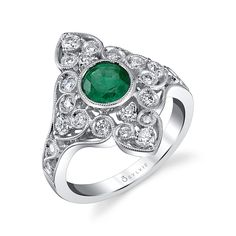 Vintage Style Emerald Engagement Ring- Milgrain accents, various shapes of round vibrant diamonds, and intricate details in swirls and hearts surrounds a stunning 1.20 carat round emerald in an elevated bezel setting. This #vintage style #engagement ring with a floral motif has a tapered shank with a total carat weight of 1.84. https://www.sylviecollection.com/vintage-style-emerald-engagement-ring-s1214em