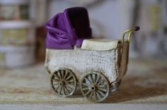This is a hand made dolly pram painted in white ,leather head and apron Has metal wheels,this miniature has then been aged to look used. Please