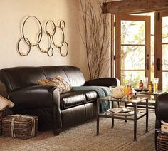 an-attractive-small-neutral-living-room-color-decorated-with-circular-metal-wall-decoration-including-double-glass-door-and-black-leather-triple-coach-fetching-with-square-table-from-glass-and-also-beige-fur-on-floor-744x669.jpg (744×669)