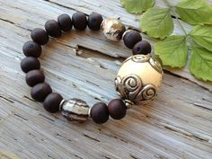 """$68 - BODHI SEED BRACELET    This bracelet is a reminder of the story of Buddha's enlightenment. The bodhi tree, was a large and very old sacred fig tree, under which the spiritual teacher Buddha achieved enlightenment, or bodhi.  This stunning bracelet is composed of rich brown bodhi seeds, a large focal nepali bead, pyrite, hill tribe silver and outback jasper. Stretch bracelet measures just over 7"""", sized to fit most wrists."""