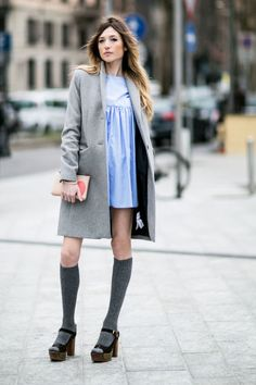 A babydoll dress is worn with a grey coat, over the knee socks, and platform sandals