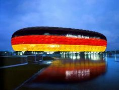 Alianz Arena. I chose this photo due to the fact it showcases the lighting on the outside of the Arena. This lighting tells us that the German National Team (Die Mannschaft) is playing a match. The Allianz arena also hosts a few german club teams, and lights up to their home colors as well.