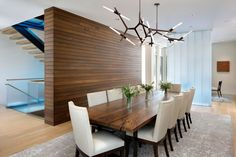 In this contemporary dining room sits beside a wood accent wall and a channel glass partition, while sculptural pendant lights add an artistic flair to the room. Glass Wall Systems, Contemporary Dining Room Sets, Tiered Seating, Living Comedor, Dining Room Lighting, Dining Rooms, Indoor Outdoor Living, Lounge Areas, Modern Interior Design