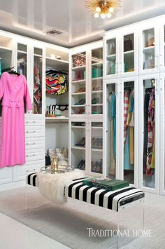 In this clean and organized closet, a black-and-white-striped bench with acrylic legs provides a perch for putting on shoes. - Photo: Michael Garland / Design: Kelly Lee