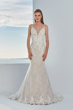 Emphasize your shape in this allover lace fit and flare gown. The deep V-neckline features illusion straps and a plunge neckline. Lace adorns the bodice and hem over the outer layer with allover details on the underlay. Also available with a raised neckline option for a more traditional look.