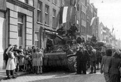 "The ecstatic inhabitants of Eindhoven (Market-Garden) smother a Guards Armoured Division tank soon after it enters the town. - ""The greeting we received in the town"" - recalled one driver, ""brought tears to our eyes."""