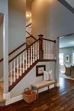 like the dark wood floor and railings with the white spindals and light walls