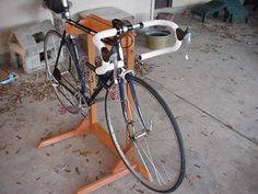 wood bike stand. Looks fairly simple (depending on your woodworking skills and the kind of wood you use). I would add feet to the back for more support in case you bumped the front. Just in case.