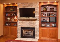 Stone fireplace with built in shelves and cabinets