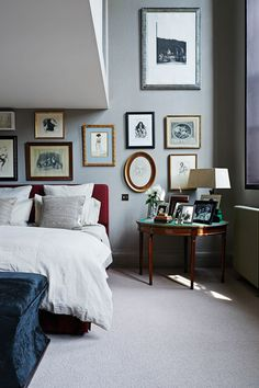 A red upholstered headboard stands out against the linen-effect wallpaper from Flamant in the main bedroom, where Gytha has created a gallery wall of pictures