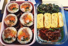 (doshirak) korean lunch box, with kimbap, and seasoned spinach, egg, and dried squid banchan (side dishes).