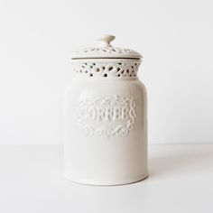 """Vintage Style Ceramic Coffee Jar. Features: Cutout embellishment on rubber-sealed lid and around rim, with a raised """"Coffee"""" label design.<b>Size:</b> 4"""" base x 3 ½"""" rim x 6 ¾"""" height<b>Color:</b> Ivory<b>Label:</b> Classic Ceramics. California Pantry. 2006 Made in China.<b>Condition:</b> Fair. The jar has a visible crack down half the front, and partial crack on the back. Both are minimal. <i>Sh..."""