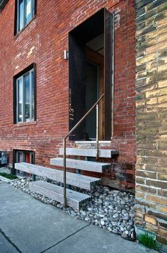 Creative entrance into 19th-century building. A portal formed by projecting steel plates lining the recessed opening; wood-slat steps float above river rocks; minimal railing. By THE CREATIVE UNION NETWORK, Toronto, Canada http://www.creative-union.net/index.php