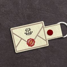 Did someone say accio keys?   [image of a white envelope with black crest and red seal. attached to a silver key ring.]  Harry Potter Hogwarts Letter ITH Key Fob Applique Embroidery Design File