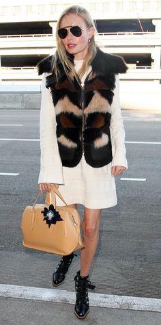 Kate Bosworth, easily one of the chicest jet-setting stars. She departed from LAX in a white bell-sleeved Frame sweater dress that she topped with a furry vest, aviators, a leather satchel, and Tod's lace-up boots.