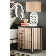 This oval nightstand from the American Drew Bob Mackie Home collection features a granite top and a pale gold finish for a look that is both modern and luxurious.