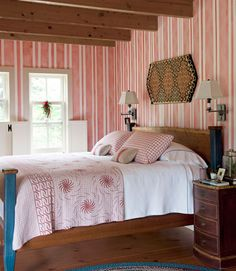 The master bedroom walls are painted in a striped pattern that echoes a hand-painted wallpaper. A penny rug is displayed above the c­ustom-made cherry bed, dressed with an antique blanket, shams, and throw pillows, all in red and white.