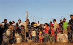 Syrian refugees crowd behind barbed wire at the dusty Turkey- Syria border in…