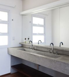As with the kitchen, the scale of the bathroom sink is far from poky. A minimal sculptural form in polished concrete, it's bold and chic.
