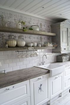 White kitchen with reclaimed wood open shelves and farm sinks