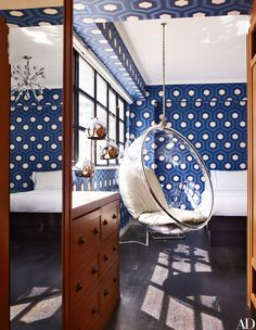 In the same home, an Eero Aarnio Bubble chair hangs in son Rex's room; the David Hicks hexagon wallpaper is by Cole & Son