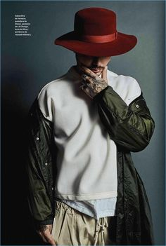 Front and center, J. Balvin wears a Versace parka with a Diesel sweater, LIU Design pants, and a Yestadt Millinery hat.