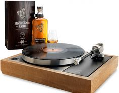 Turntable with a whisky wood plinth, made from the solid oak casks with a bottle with 40 years old Highland Park whisky