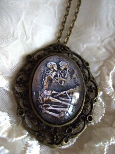 Ancient Love Embracing Skeletons Portrait Cameo Necklace.