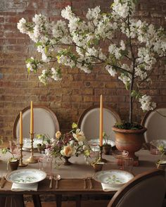 """""""One of the questions brides ask me most often is how they can decorate the space above the tables in a high-ceilinged venue,"""" says Merrick. Her answer: reach-for-the-sky potted branches, such as the flowering apple one below, which offer fullness yet still allow for cross-table conversation. And the concept isn't season-specific, notes Merrick, who suggests a leafier version, like maple, in the summer; a fruiting tree like quince in the fall; and bare branches hung with votives in the…"""