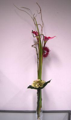 Sia School: composición en vertical con dos callas, un allium, hojas de iris, una rama seca, dos varas de equisetum, una cabeza de hydrangea y una hoja de hosta. El resultado es muy elegante