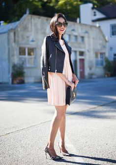 A feminine dress is worn with a cropped moto jacket, leopard print heels, and oversized sunglasses